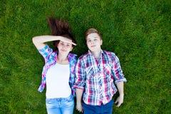 Pares adolescentes jovenes en el verde Fotos de archivo