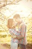 Pares adolescentes jovenes en los manzanos del flor de la primavera Fotografía de archivo libre de regalías