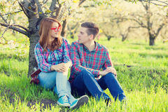 Pares adolescentes jovenes en los manzanos del flor de la primavera Foto de archivo