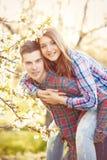 Pares adolescentes jovenes en los manzanos del flor de la primavera Fotos de archivo libres de regalías