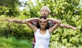 Pares adolescentes jovenes en parque verde. Imagen de archivo libre de regalías