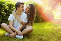 Pares adolescentes jovenes preciosos en el amor que se divierte en césped en parque Fotografía de archivo