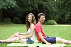 Pares adolescentes jovenes que se relajan en un parque verde enorme Foto de archivo libre de regalías