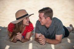 Pares adolescentes jovenes relajados en la playa Imagen de archivo libre de regalías