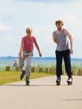Pares adolescentes junto en patines Foto de archivo