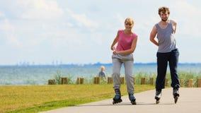 Pares adolescentes junto en patines Imagen de archivo libre de regalías
