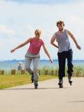 Pares adolescentes junto en patines Foto de archivo libre de regalías