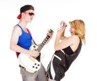 Pares adolescentes - muchacha que toma imágenes de su novio con Guit Imagenes de archivo
