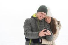 Pares adolescentes ocupados en la mirada de la pantalla móvil Fotos de archivo