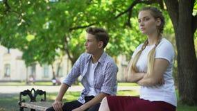 Pares adolescentes ofendidos que sentam-se no parque no banco, ignorando-se, conflito video estoque