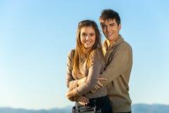 Pares adolescentes que abrazan al aire libre. Fotografía de archivo