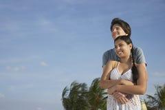 Pares adolescentes que abrazan en la playa Fotografía de archivo
