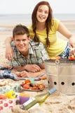 Pares adolescentes que apreciam o assado na praia junto imagens de stock royalty free