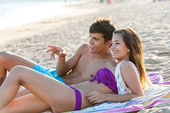 Pares adolescentes que apreciam a tarde na praia. imagem de stock royalty free