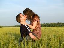 Pares adolescentes que beijam no campo Fotografia de Stock Royalty Free