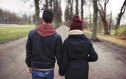 Pares adolescentes que caminan en el parque que lleva a cabo las manos Imagen de archivo libre de regalías