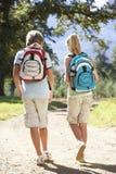 Pares adolescentes que caminan a través del campo visto de la parte posterior Fotografía de archivo