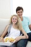 Pares adolescentes que comen las hamburguesas y las fritadas Fotografía de archivo libre de regalías
