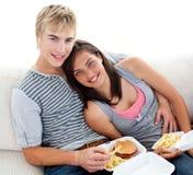 Pares adolescentes que comen las hamburguesas y las fritadas en el país Fotos de archivo libres de regalías