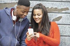 Pares adolescentes que comparten el mensaje de texto en el teléfono móvil Imagenes de archivo