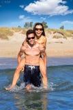 Pares adolescentes que correm às cavalitas na praia do verão Imagens de Stock Royalty Free