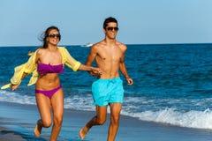 Pares adolescentes que corren junto en la playa. foto de archivo
