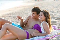 Pares adolescentes que disfrutan de tarde en la playa. Imagen de archivo libre de regalías