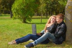 Pares adolescentes que estudian con una computadora portátil en el parque Imágenes de archivo libres de regalías