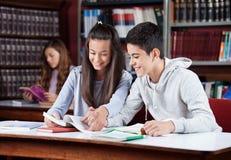 Pares adolescentes que estudian junto en biblioteca Imagen de archivo libre de regalías