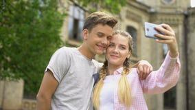 Pares adolescentes que fazem o selfie, usando o telefone durante sightseeing, levantando junto filme