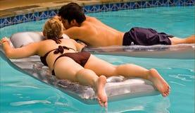 Pares adolescentes que flotan en piscina Imagen de archivo libre de regalías