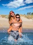 Pares adolescentes que gozan a cuestas en la playa del verano Imagen de archivo libre de regalías