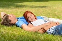 Pares adolescentes que gozan del sol que miente en hierba Fotografía de archivo libre de regalías