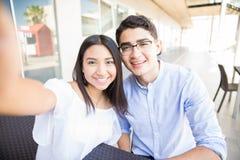 Pares adolescentes que hacen clic memorias del amor en la alameda de compras Foto de archivo