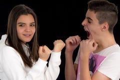 Pares adolescentes que imitan una lucha III Foto de archivo