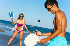 Pares adolescentes que juegan con fuerza a tenis de la playa de la bola. Fotografía de archivo