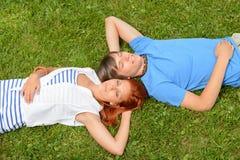 Pares adolescentes que mienten en hierba Imagen de archivo libre de regalías
