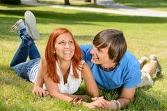 Pares adolescentes que mienten en la hierba que ríe junto Foto de archivo libre de regalías