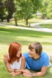 Pares adolescentes que mienten en parque soleado Imágenes de archivo libres de regalías