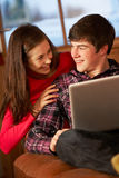 Pares adolescentes que relaxam no sofá com portátil Imagem de Stock Royalty Free