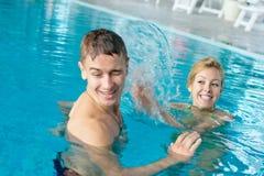 Pares adolescentes que salpican en la piscina Imagen de archivo libre de regalías