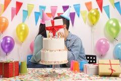 Pares adolescentes que se besan detrás de un presente Imagenes de archivo