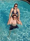 Pares adolescentes que se divierten en la piscina Imagen de archivo libre de regalías