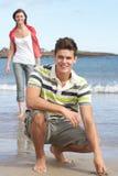 Pares adolescentes que se divierten en la playa Imagen de archivo libre de regalías