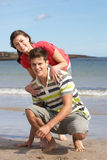 Pares adolescentes que se divierten en la playa imagen de archivo