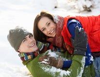 Pares adolescentes que se divierten en nieve Fotografía de archivo libre de regalías