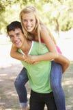 Pares adolescentes que se divierten en parque junto Foto de archivo libre de regalías