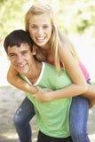 Pares adolescentes que se divierten en parque junto Fotografía de archivo