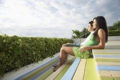 Pares adolescentes que se sientan en cubierta Imagen de archivo libre de regalías