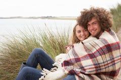 Pares adolescentes que se sientan en dunas de arena Imagen de archivo libre de regalías